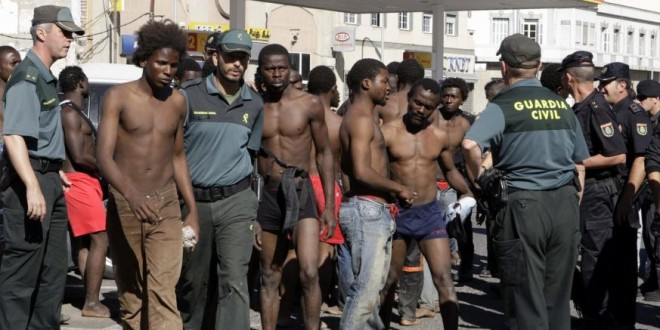 Des-agents-de-la-Guardia-Civil-entourent-des-subsahariens-qui-viennent-de-franchir-la-barrière-660x330