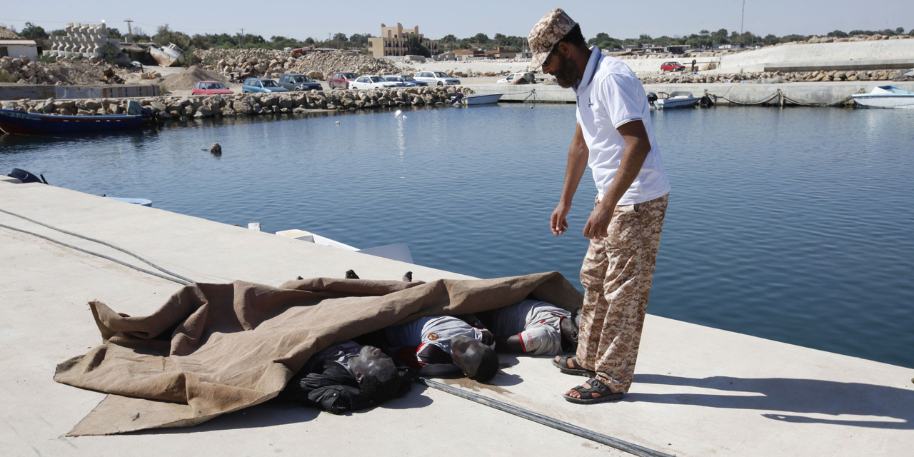 ATTENTION EDITORS - VISUAL COVERAGE OF SCENES OF INJURY OR DEATH A man inspects the bodies of three African migrants that were recovered by the Libyan coastguard, after their boat sunk off the coastal town of Garaboly, east of Tripoli, September 15, 2014. According to a coastguard spokesperson, there were 108 immigrants on the boat, of which 102 were rescued while three were found dead and another three missing. REUTERS/Ismail Zitouny (LIBYA - Tags: SOCIETY IMMIGRATION DISASTER) TEMPLATE OUT - RTR46B7G
